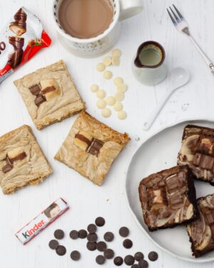 Kinder Selection - A white background, with a Kinder Bueno Bar, 3 Kinder Bueno Blondies, 3 Kinder Bueno Brownies, a cup of tea, a fork, milk jug and chocolate chips.